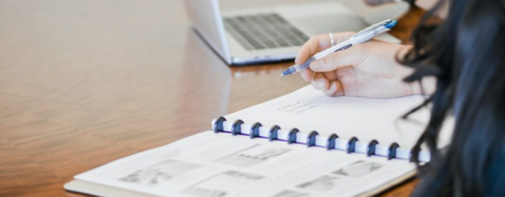 woman writing financials in notebook